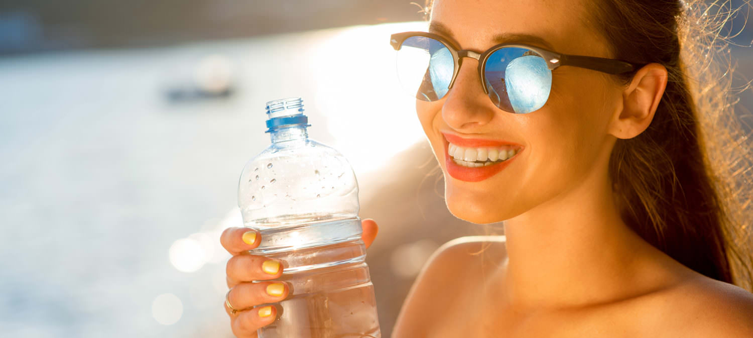 Young woman drinking sparkling water from transparent bottle on the beach on sunset