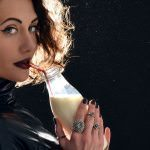 Portrait of beautiful fashion woman drinking milk from the bottle with straw on dark background